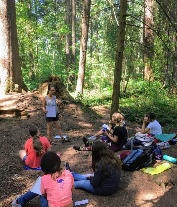 Our outdoor classroom with girls taking notes in the forest.